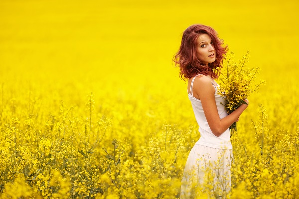 Beautiful Ukrainian girl posing with a bouquet of flowers in the field