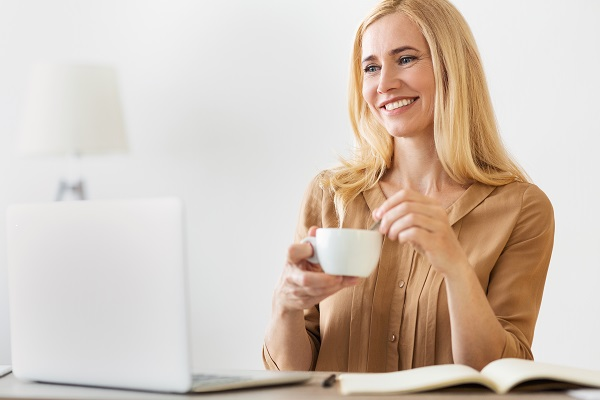 Happy entrepreneur Ukrainian woman drinking coffee while working on a laptop